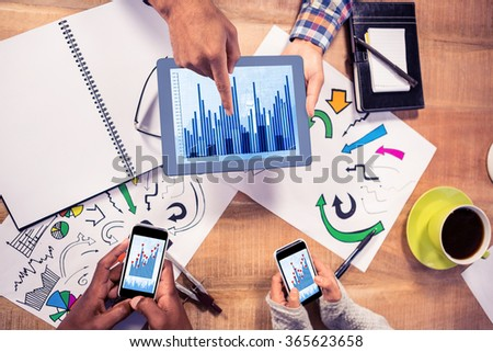 Blue data against overhead view of creative business team working at desk - stock photo