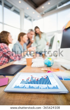 Blue data against tablet in the foreground with business people in the background - stock photo