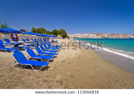 Blue deck chairs on the public beach of Crete, Greece - stock photo