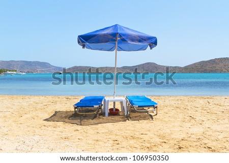 Blue deckchairs under parasol at Aegean Sea - stock photo