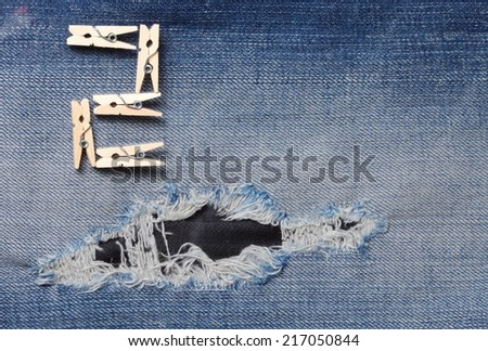 Blue denim jeans with the clothespin made from wood in the scene present the old denim look and old damaging fabric that shown detail of texture background and wording 2 from clothespin.  - stock photo