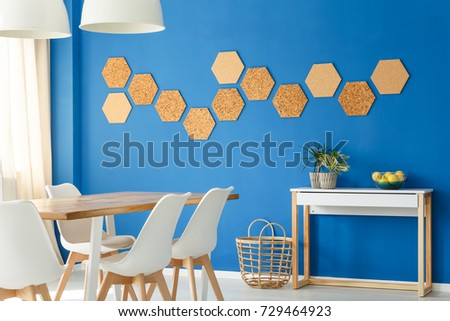blue dining room with cork wall decor and basket on floor next to simple cupboard - Cork Dining Room Design