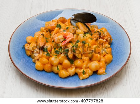 blue dish with gnocchi,seafood and tomatoes sauce - stock photo
