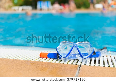 Blue diving mask and snorkel at the swimming pool - stock photo
