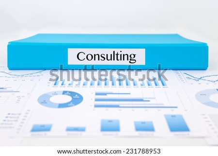 Blue document binder with Consulting word place on graphs analysis and business reports