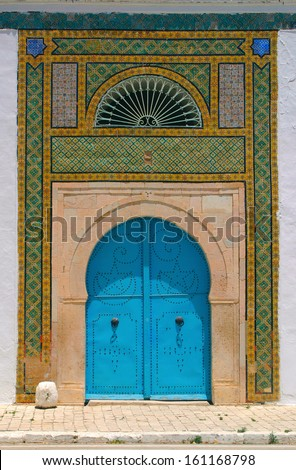Blue door and detail of North African arab architecture - ornaments around the doors - stock photo