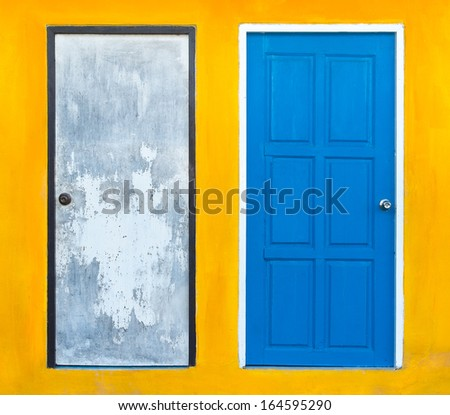 Blue door and gray with bright yellow walls. - stock photo