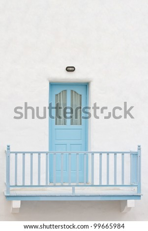 Blue door and terrace on white house - stock photo