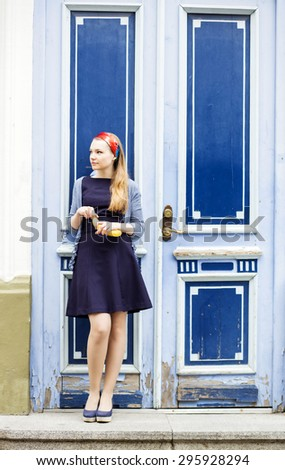 Blue door behind the girl with banana - stock photo