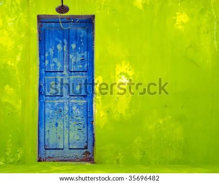 Blue Door in Shabby Green Wall - stock photo