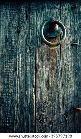 Blue door of the stable. Old vintage blue grey painted wooden door background with metallic ring as handle at the upper right. - stock photo