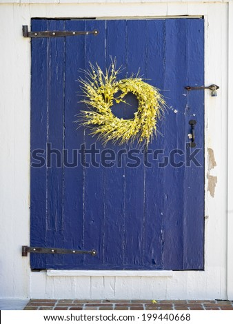 Blue door with Spring wreath of yellow flowers. - stock photo