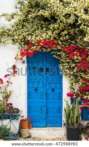 Blue door with traditional ornament as symbol of Sidi Bou Said and flowers