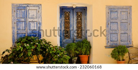 Blue doors, window shutters and decorative plants in some village on Samos island. - stock photo