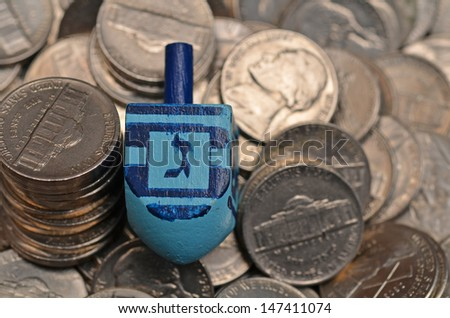 blue dreidel,, on shiny nickles with the letter gimmel showing. Gimmel lets one win everything in the pot...a game played during the Jewish Holiday Hanukkah/Dreidel and Winnings - stock photo