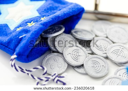 Blue dreidel with silver tokens on a white background - stock photo