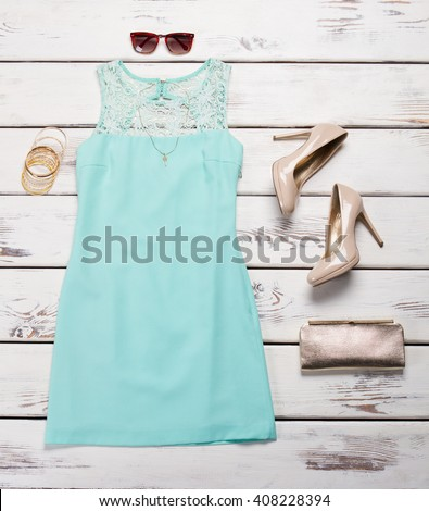 Blue dress and heel shoes. Shelf with dress and footwear. Lace insert dress with accessories. Luxury outfit for young ladies. - stock photo