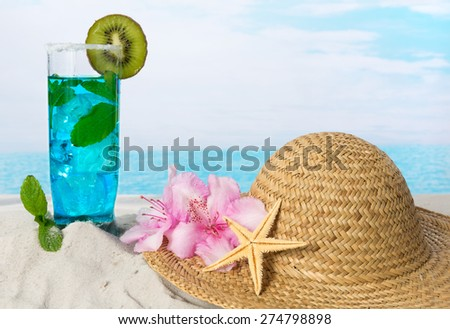 Blue drink with green mint leaves and sunhat on the beach