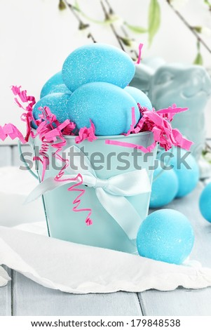 Blue Easter eggs in a blue tin bucket. Shallow depth of field. - stock photo