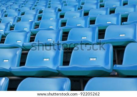 Blue Empty plastic seats at stadium open door sports arena - stock photo