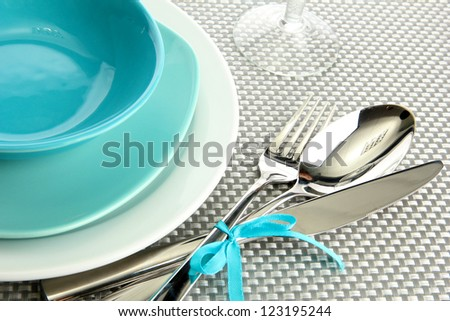 blue empty plates with fork, spoon and knife on a grey tablecloth - stock photo