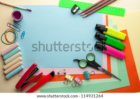 Blue empty sheet with lots of stationery objects makes a great copy space for you message or drawing. - stock photo