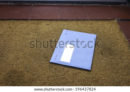 Blue envelope from the Dutch tax office on the door mat - stock photo
