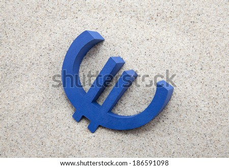 Blue euro symbol in the sand - stock photo