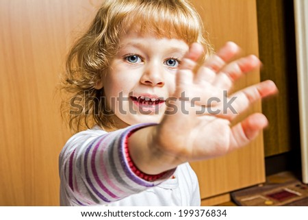 Blue-eyed, adorable little girl is greeting waving her hand. - stock photo