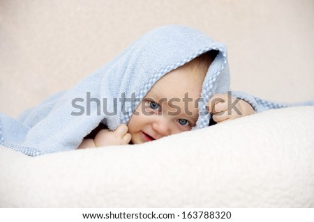 Blue eyed baby boy hiding under a blue blacket looking at the camera on a soft peach coloured background - stock photo