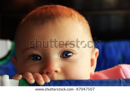 Blue-eyed baby peeking over blue pack and play crib - stock photo