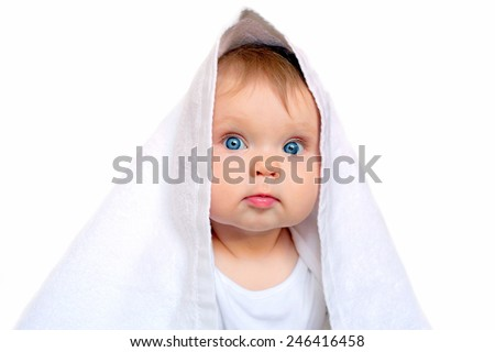 Blue-eyed baby under the white towel after bath. Isolated on white background. - stock photo
