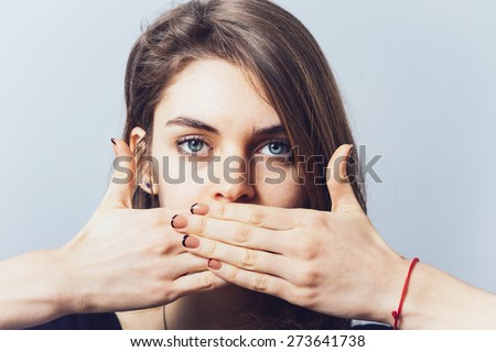 blue-eyed brunette girl covers her mouth with her hands - stock photo