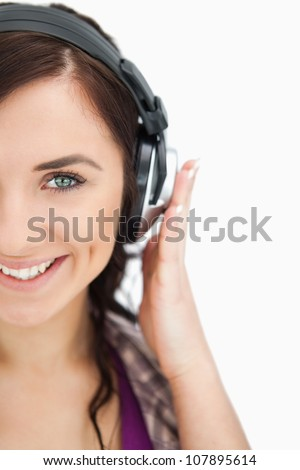 Blue eyed brunette smiling while wearing headphones against white background