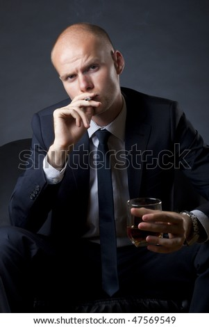 blue eyed businessman siting on a sofa and smoking a cigarette and drinking whiskey
