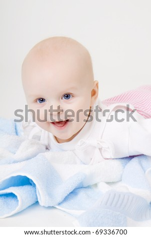 blue-eyed happy baby with a blue towel on the floor
