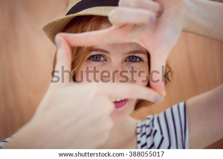 Blue eyed hipster looking through her hands like a camera