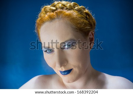 blue-eyed red-haired woman with blue lips on a blue background - stock photo