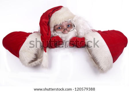 Blue-eyed Santa Claus leaning against white sign and  holding a blank text space