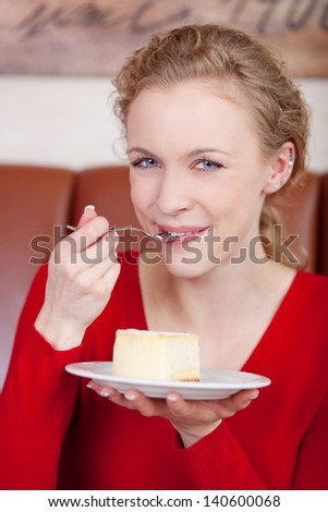 blue eyed woman eating cheese cake in a caf�© - stock photo