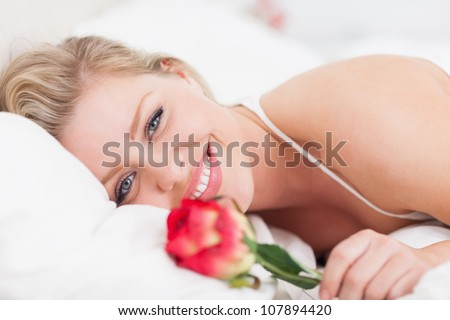 Blue eyed woman smiling with a rose in a bed - stock photo