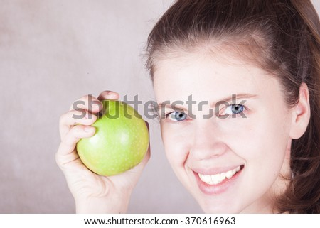 blue eyed young woman smiling with green apple in hand