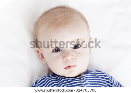 Blue eyes baby looking to the camera - stock photo