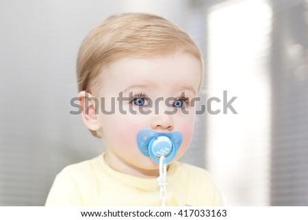 Blue eyes baby with pacifier at home