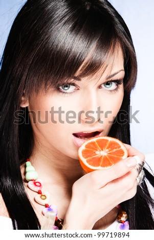 blue eyes girl hold half of orange in hand looking at camera studio shot - stock photo