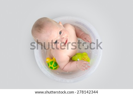 Blue eyes little girl in the bathing bucket  looking at the camera and smiling. Happy baby having a bath and playing with rubber toys. - stock photo