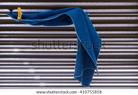 Blue fabric is drying with small peg on the toilet wall. - stock photo