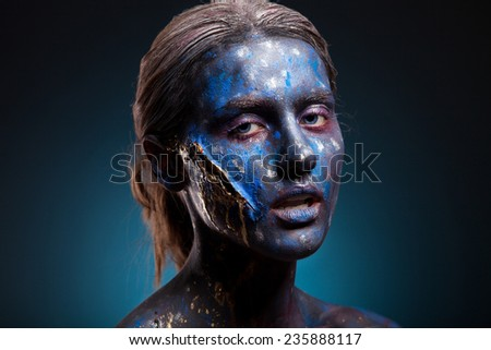 Blue face art woman with gold scar on face. Girl painted on blue color. Portrait