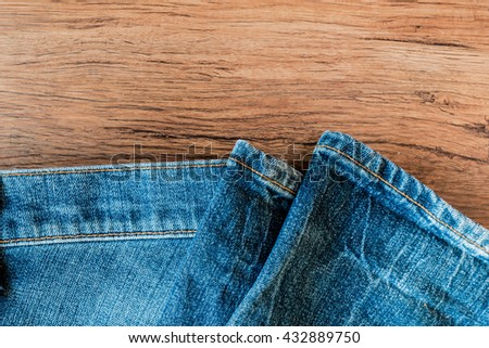 Blue Faded Heavy Worn Denim / Jeans in Wooden Background - stock photo