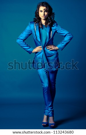 Blue fashion - beautiful young girl in blue dress over blue background - stock photo